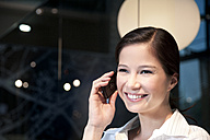Smiling young businesswoman on the phone - TOYF001251