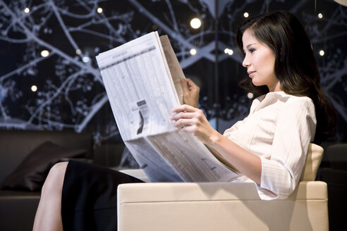 Young businesswoman sitting in armchair reading newspaper - TOYF001254