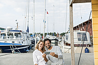 Germany, Luebeck, smiling couple at marina with smartphone - FMKF001857