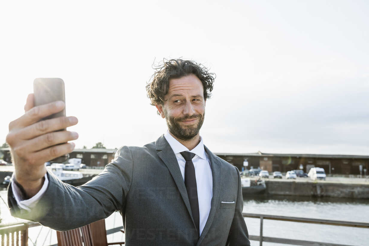 Germany, Luebeck, businessman at harbor taking a selfie - FMKF001865 - Jo Kirchherr/Westend61