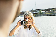 Germany, Luebeck, woman taking picture at the waterside - FMKF001893