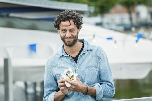 Smiling man holding a fish sandwich - FMKF001875