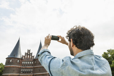 Germany, Luebeck, man taking picture in front of the Holsten Gate - FMKF001881