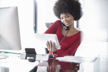 Young woman on the phone holding digital tablet at desk - ZEF007130