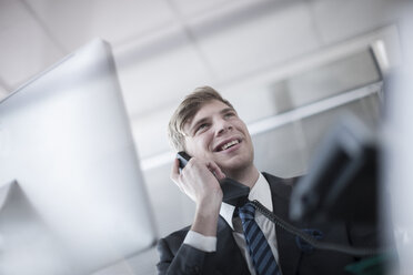 Smiling businessman talking on phone in office - ZEF007136