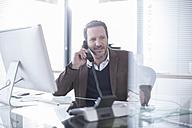 Businessman talking on phone in office - ZEF007141