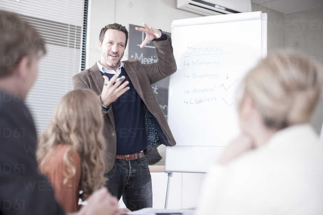 Businessman at flip chart talking to colleagues - ZEF007148 - zerocreatives/Westend61
