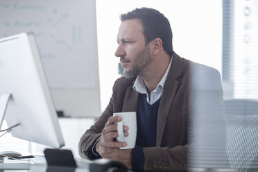 Businessman at desk looking at computer screen - ZEF007153