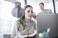 Woman in office working on laptop wearing headphones - ZEF007167