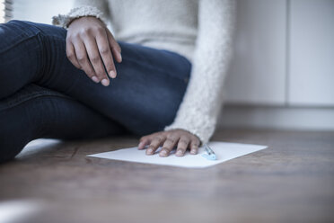 Close-up of woman sitting on office floor with sheet of paper - ZEF007172