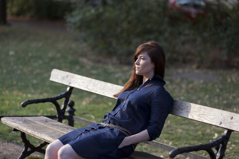 Portrait of woman sitting on a park bench - HCF000145