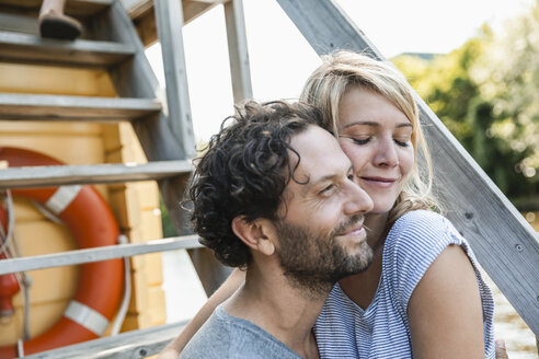 Happy couple hugging on a house boat - FMKF001911