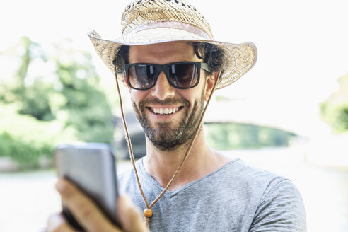 Smiling man wearing straw hat and sunglasses holding cell phone - FMKF001915