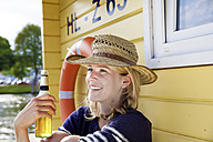Smiling woman on a house boat with beer bottle - FMKF001938