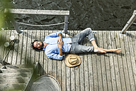 Man lying on platform at the waterside - FMKF001967
