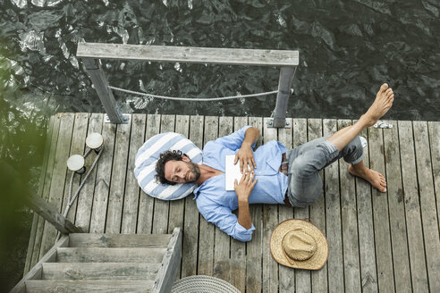 Man lying on platform at the waterside - FMKF001970