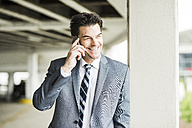 Portrait of smiling businessman telephoning with smartphone - UUF005349