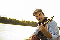 Portrait of man playing guitar at riverside in the evening - UUF005384