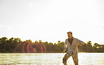Man wading in the water of a river at evening twilight - UUF005389