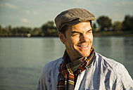 Portrait of smiling man wearing cap standing in front of a river at evening twilight - UUF005392