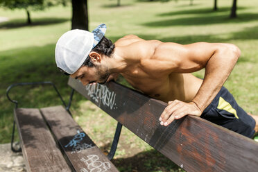 Athletic young man doing workout in the park - MGOF000487