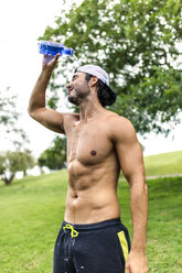 Athletic young man refreshing after training in the park - MGOF000555