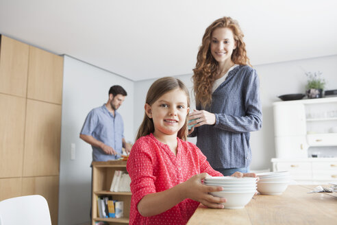 Portrait of little girl laying the table in the kitchen with her parents in the background - RBF003366