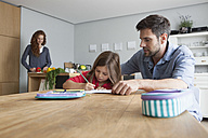 Little girl doing homework at the kitchen table while her father watching her - RBF003370