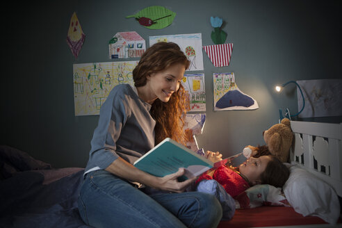 Mother reading a bedtime story for her little daughter - RBF003380