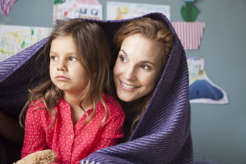 Portrait of smiling mother and her unhappy little daughter in children's room - RBF003384
