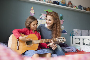 Little girl playing guitar while her mother listening - RBF003386