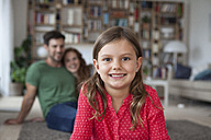 Portrait of smiling little girl and her parents in the background in the  living room - RBF003389