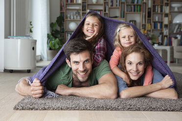 Portrait of couple with her little daughters lying together on the floor of the living room covered by a blanket - RBF003394