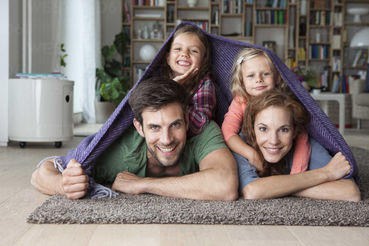 Portrait of couple with her little daughters lying together on the floor of the living room covered by a blanket - RBF003394 - Rainer Berg/Westend61
