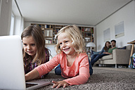 Two little sisters lying on the floor at living room with laptop while her parents sitting in the background - RBF003398
