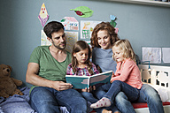 Couple and little daughters sitting together on bed in children's room reading a book - RBF003401
