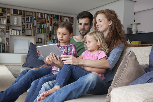 Couple sitting with their with two little daughters on couch in the living room looking at digital tablet - RBF003417