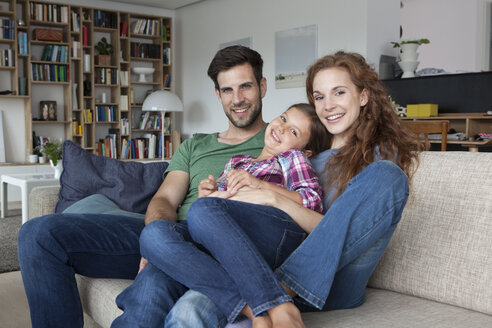 Portrait of happy couple and little daughter on the couch at home - RBF003422