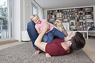 Man lying on the floor at living room playing with his little daughter - RBF003426