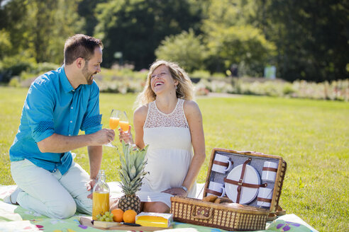 Happy couple having a picnic in park, pregnant woman - ROMF000153