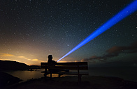 Spain, Ortigueira, Loiba, silhouette of a man sitting on bench under starry sky with blue ray - RAEF000355
