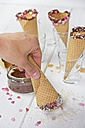 Ice-cream cones, chocolate, sugar hearts, hand dipping cone in coconut flakes - YFF000450