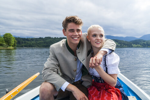 Germany, Bavaria, portrait of young couple sitting in a rowing boat on Staffelsee - TCF004859