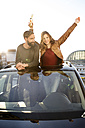 Happy couple with beer bottle looking through sunroof of a car - PESF000164