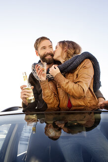 Happy couple looking through sunroof of a car sharing a scarf - PESF000167