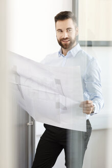 Man in office holding construction plan - PESF000121