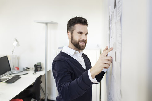 Man in office pointing at wall with papers - PESF000080