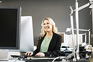 Smiling blond woman working at desk in office - PESF000108
