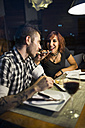 Young woman feeding her boyfriend  in modern restaurant - JASF000004