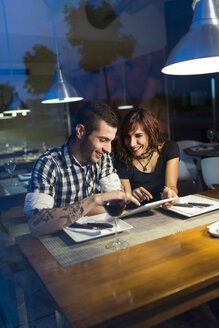 Young couple in modern restaurant  with digital tablet at evening twilight - JASF000005